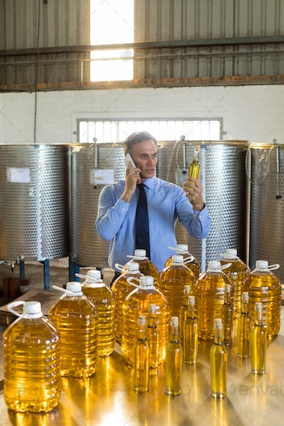 Manager talking on mobile phone while examining olive oil