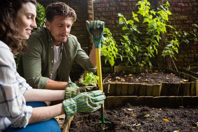 Couple interacting with each other while gardening in the garden