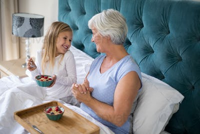 Granddaughter and grandmother interacting while having breakfast