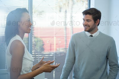 Male and female executives interacting with each other near window