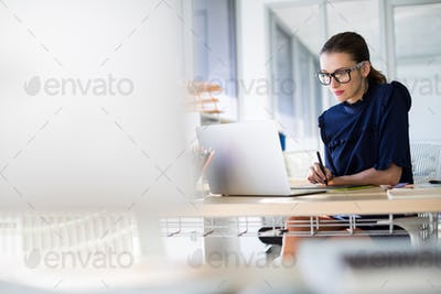 Female executive working over laptop and graphic tablet at her desk