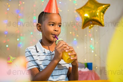 Thoughtful boy drinking juice during birthday party