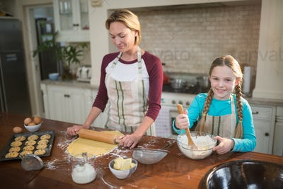 Smiling mother and daughter preparing cookies in kitchen