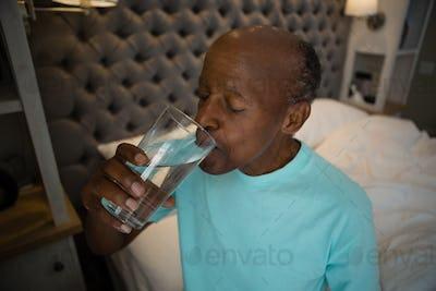 Senior man taking medicine while sitting at home