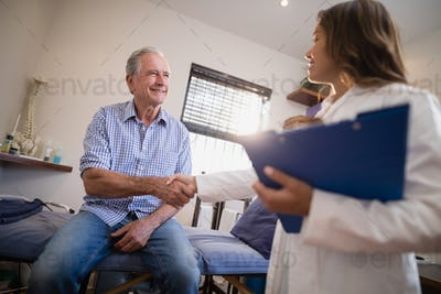 Low angle view of female therapist and senior male patient shaking hands