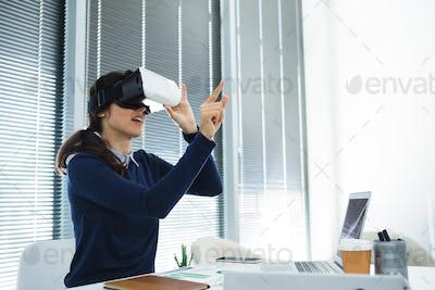 Female executive using virtual headset at desk