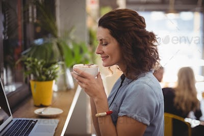 Young woman smelling coffee while sitting at cafe