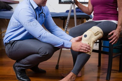 Physiotherapist examining his patients knee