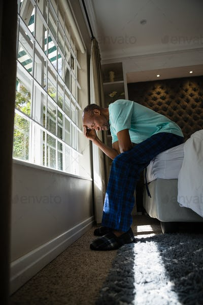 Full length side view of serious senior man sitting on bed by window