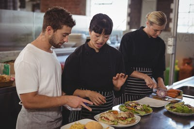 Female chef talking with waiter by colleague at kitchen