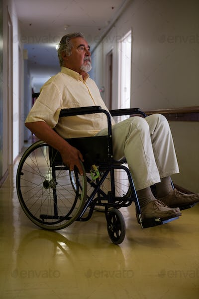 Thoughtful senior man sitting on wheelchair in corridor