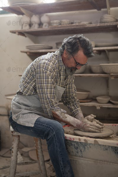 Male potter molding clay