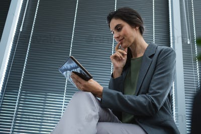 Low angle view of female executive using digital tablet