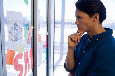 Male executive reading sticky notes on glass door