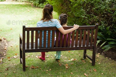 Rear view of woman and girl sitting on wooden bench