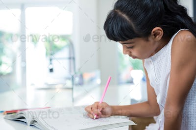 Side view of girl drawing in book
