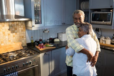 Affectionate couple with eyes closed embracing while standing in kitchen