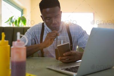 Man using mobile phone while having drinks