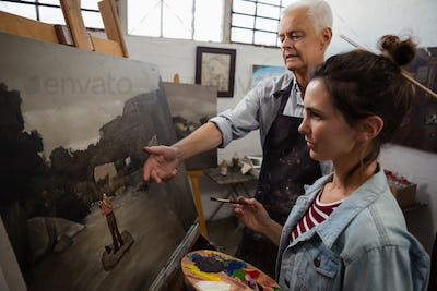 Senior man interacting while artist painting on canvas