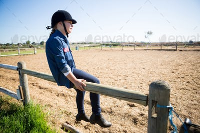 Girl sitting on wooden fence in the ranch