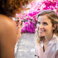 Woman applying makeup to bride in yard