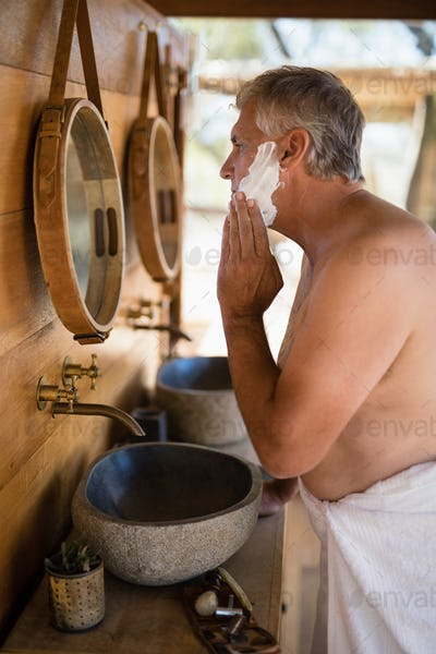 Man applying shaving cream on his face in cottage