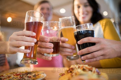 Low angle view of happy friends toasting drinks in restaurant