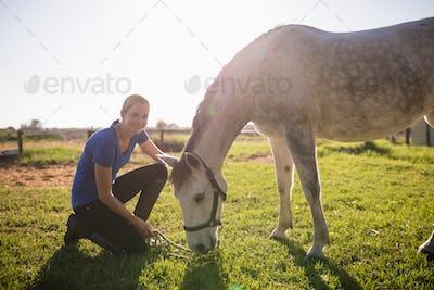 Portrait of smiling jockey stroking horse at barn