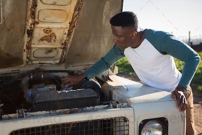 Man repairing car at countryside