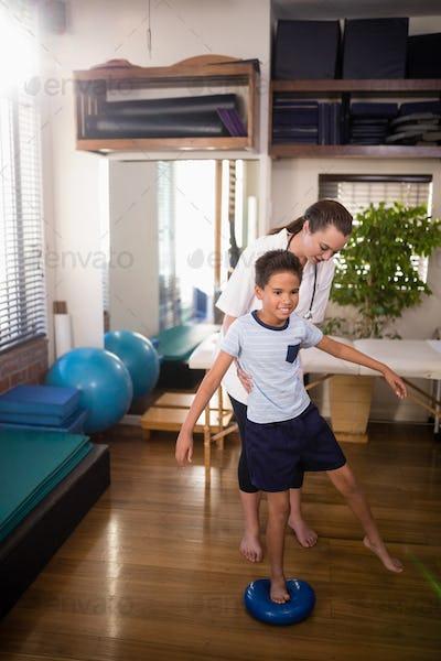 Female therapist holding boy standing on blue stress ball