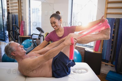 Smiling female therapist looking at male patient pulling resistance band while lying on bed