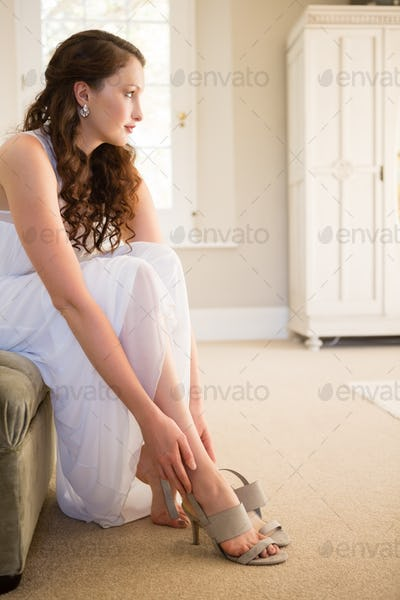 Bride putting on sandals while sitting at home