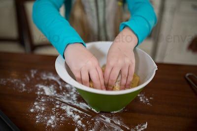 Girl kneading dough in kitchen