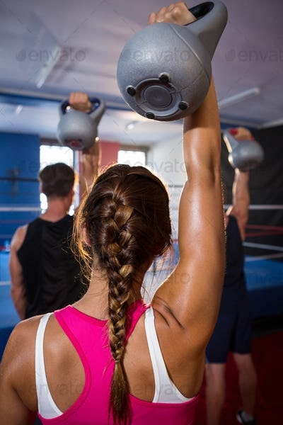 Rear view of young female athlete lifting kettle