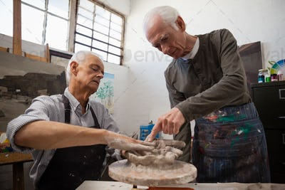 Senior man assisting in making pottery during drawing class