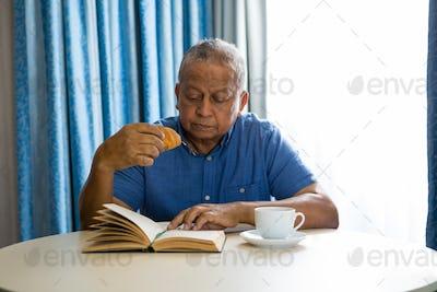 Senior man eating croissant while reading book in nursing home