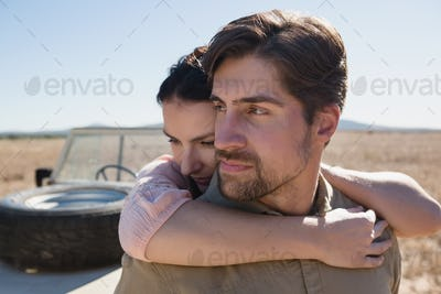 Man with woman by off road vehicle on landscape