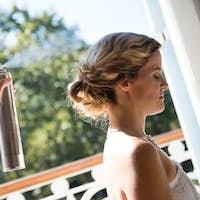 Bridesmaid applying hairspray to bride in dressing room
