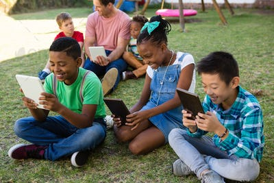 Children using tablet computer with man at park