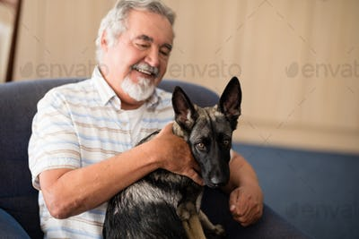Happy senior man stroking puppy while sitting on armchair
