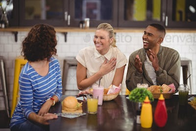 Cheerful young friends talking while sitting with food and drink at coffee shop