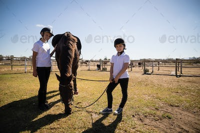 Smiling girls standing in ranch with brown house