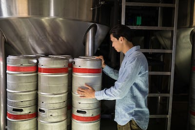Manager checking beer keg in warehouse