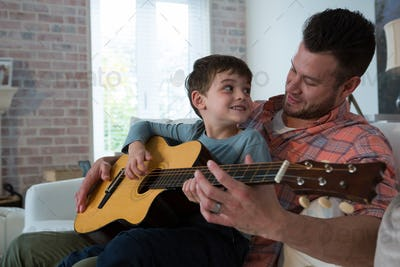 Father assisting his son in playing guitar