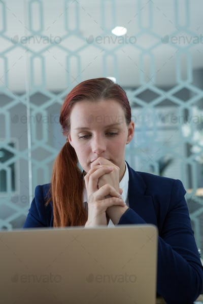 Thoughtful businesswoman using laptop at desk