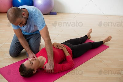 Instructor guiding female student in exercising at yoga studio