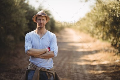 Confident young man standing on dirt road at farm