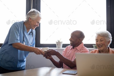 Smiling healthcare worker serving coffee to senior man sitting by friend
