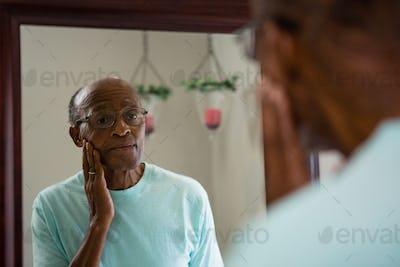 Concerned senior man rubbing cheek while looking into mirror
