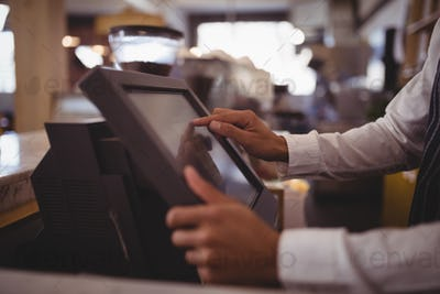 Midsection of waiter touching computer monitor at counter